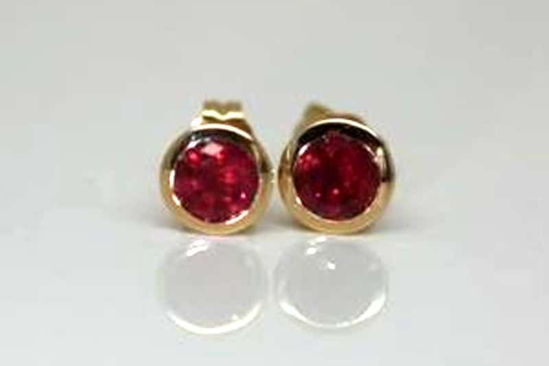 70th birthday Earrings present. Fair Trade rubies in a handmade recycled 18 carat yellow gold bezel setting.