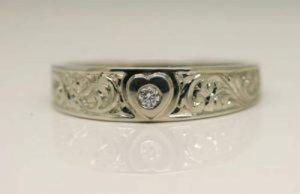 ring image. Handmade band style tapered ring with a central raised heart set with an Argyle origin diamond. The ring is hand engraved with swirls on either side of the heart.