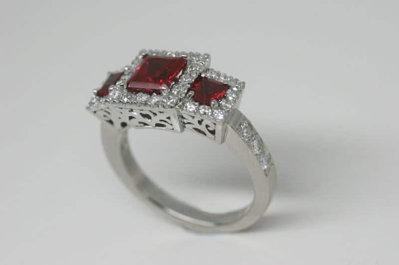 Recycled platinum trilogy engagement ring featuring synthetic rubies