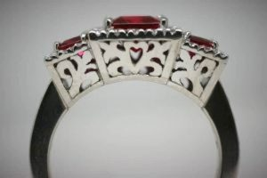 Side view of synthetic ruby trilogy ring showing detailed, pierced undercarriage