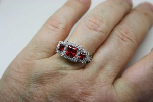 View of platinum synthetic ruby and diamond trilogy engagement ring on the wearer's finger