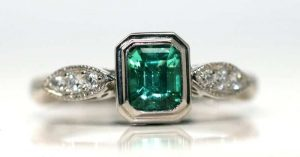 Bezel set emerald ring with shoulder set diamonds surrounded with a milgrain finish.