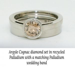 Image of an engagement ring with a bezel set Argyle cognac diamond set in recycled palladium, paired with a matching wedding ring