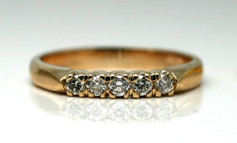 Image of an 18 carat gold wedding ring bead-set with five white accent diamonds