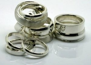 Image of a collection of machine pressed wedding rings in a variety of profiles and finishes