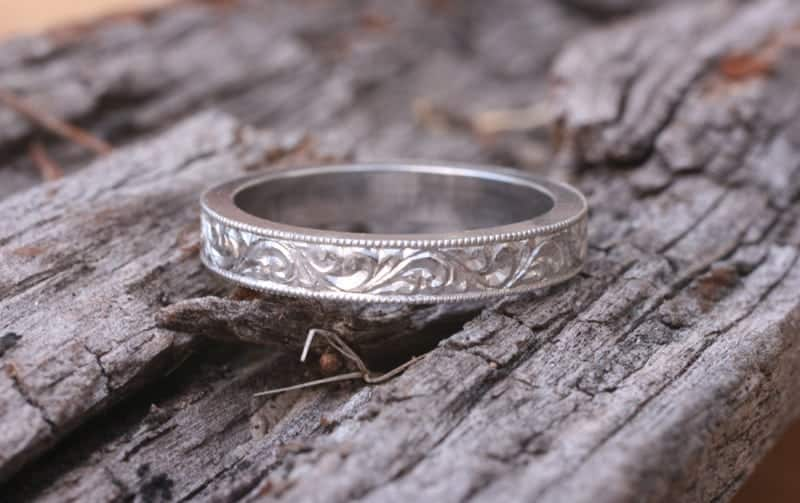 Flat profile platinum wedding ring with intricate engraving and milgrain edging