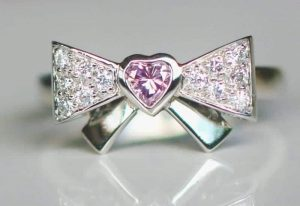 Photo of a cute-as-a-button bow ring features a heart-shaped Argyle pink diamond at its center with 'white' Argyle diamonds set into the bow.