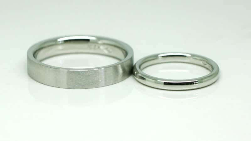 Image of two platinum wedding rings. One is a flat band with a wire-brushed finish. The other is a round profile band with a polished finish.