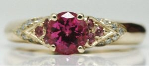 Image of a synthetic pink sapphire with natural pink sapphire and Argyle white diamond accent stones all set in a yellow gold ring