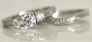 Image of a trilogy style Argyle white diamond engagement ring and matching wedding ring all in recycle palladium
