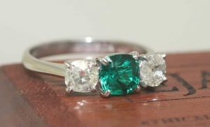 Image of a radiant cut synthetic emerald claw set and flanked by vintage white diamonds all set in a trilogy style recycled platinum ring