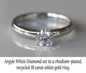 Image of a rhodium plated white gold engagement ring featuring a claw set Argyle white diamond