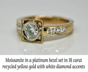 Image of an 18 carat yellow gold engagement ring with a moissanite main stone and small white accent diamonds