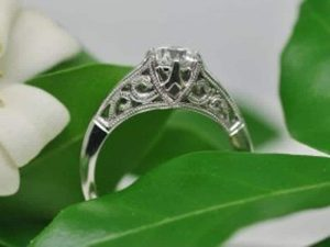 Side view of a diamond solitaire ring with saw-pierced, engraved and milgrained undercarriage