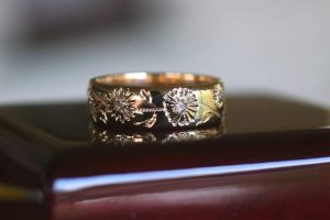 Image of a wide recycled 18 carat yellow gold wedding ring featuring hammer set diamonds with engraved daisy flowers, stems and leaves