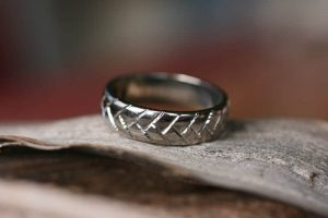 Image a wide wedding ring in recycled palladium featuring a tractor tyre engraved pattern