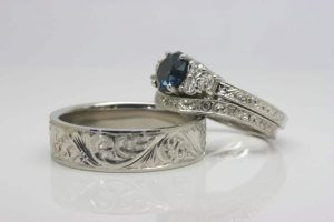 Image of elaborate scroll style engraving on a matching his and hers platinum engagement and wedding ring set