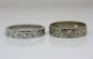 Image of engraved wedding rings featuring vines and leaves and flower petals around hammer set diamonds
