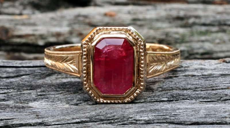 Image of an emerald cut Fair Trade ruby bezel set in a recycle 18 carat gold engagement ring that features milgrain and leaf pattern engraving