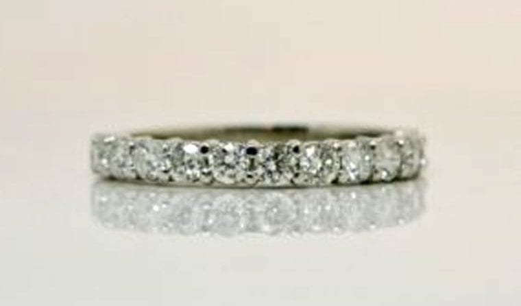 Ring image: Handmade wedding ring. With a half-eternity style, this shared-prong ring features a collection of claw set white diamonds along its band.