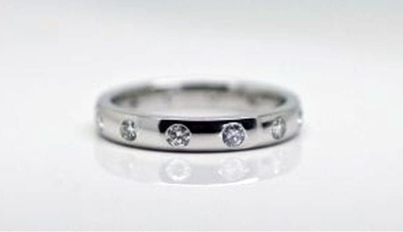 Ring image: Handmade wedding ring. With its polished metal band, this ring features a collection of small white diamonds, hammer set into the band.