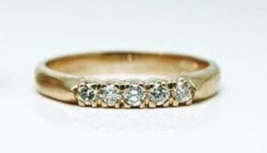 Image of a recycled 18 carat yellow gold commitment ring featuring 5 claw set white diamonds