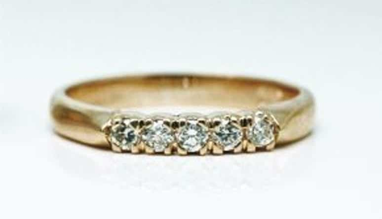 Ring image: Handmade wedding ring. With a band of 18 carat yellow gold, this ring features an assortment of small white diamonds claw set into the front.