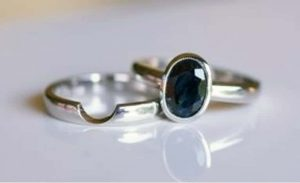 Image of a cut out style simple wedding band fitted to a simple bezel set oval sapphire engagement ring