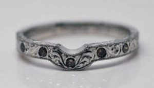 Image of a fitted wedding ring made with recycled platinum, diamond set and engraved