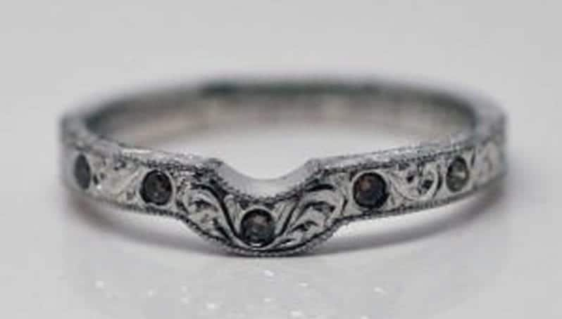 Ring image: Handmade wedding ring. This fitted wedder features diamonds set into the front of the band, custom engraving and milgrained edges.