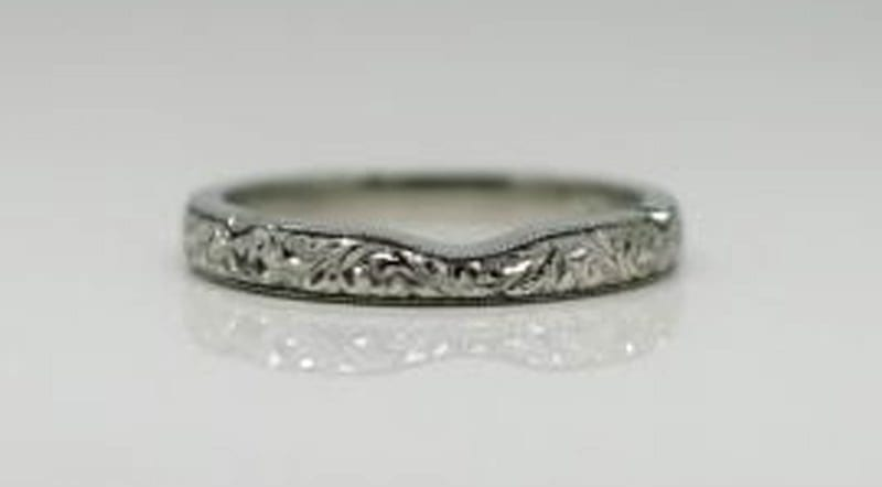 Ring image: Handmade wedding ring. With its gently shaped design, this fitted wedder features a custom engraving along the band, as well as milgrained edges.