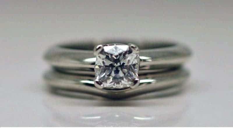 Four claw solitaire ring with a cushion cut diamond and round profile band with matching wedding ring