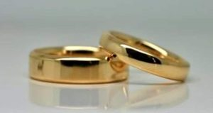 Rings image: Handmade wedding rings. Made from recycled 18 carat yellow gold, these wedding rings feature polished finishes and half-round profiles.