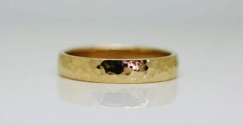 Ring image: Handmade wedding ring. Crafted from recycled 18 carat yellow gold, this simple wedding ring features a beaten texture across the band.