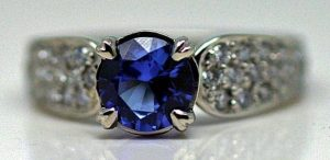 Image of a gorgeous vivid blue of Tanzanite set in a platinum ring with pave set diamonds in the band
