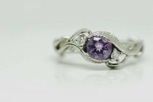 Ring image: Handmade engagement ring. Crafted from recycled platinum, this nature-inspired engagement ring features a branch-like design and a central amethyst. On each side of the amethyst is a claw set recycled white diamond.