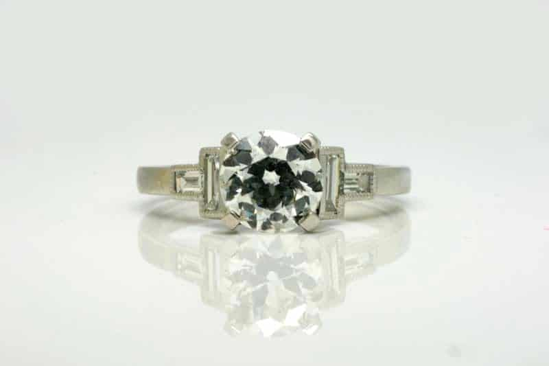 Vintage style ring in platinum featuring a round white diamond flanked by four white baguette diamonds