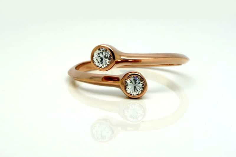 Rose gold bypass style ring with a knife-edge profile band featuring two vintage diamonds