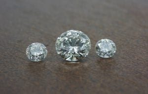 Image of three diamonds. These are CVD lab created diamonds. A centre half carat GVS with 3mm G/H Si side diamonds.