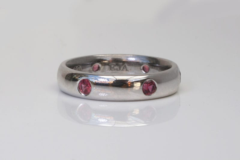 Image of a polished finished, half-round platinum wedding ring hammer set with Fair Trade rubies