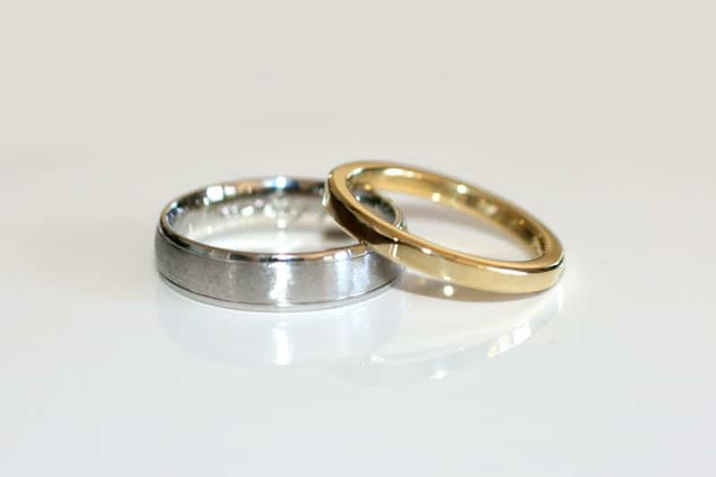 His and hers wedding rings, one in yellow gold and one in palladium with a wire brushed finish