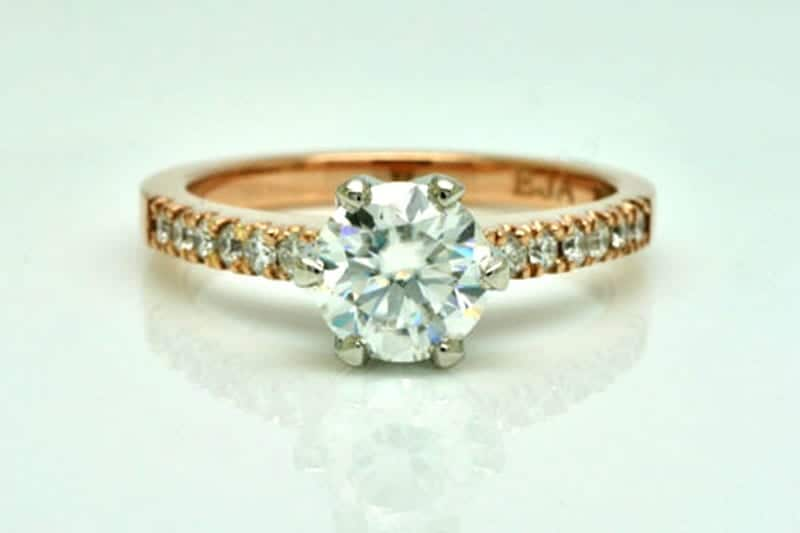 Image of a moissanite and rose gold engagement ring with six white accent diamonds set into each shoulder