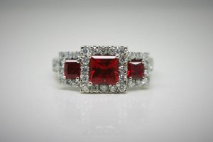 Ring image: Handmade engagement ring. The pineapple ring is a trilogy ring made from recycled platinum. Each of the main gems are lab-grown rubies in claw settings, and each is surrounded by Argyle white diamonds.