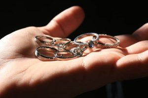 Image of many wedding and engagement rings held in the palm of someone's hand