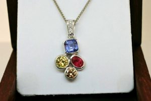 Photo of a pendant gift for her. Birthstones for the family - Tanzanite (blue), Sapphire (yellow), Ruby (red) and Diamond (cognac) - with accent white diamonds in the bale - all set in recycled platinum