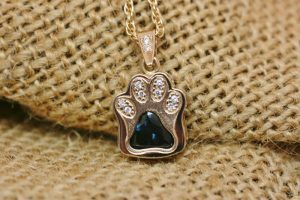 Photo of a recycled 18 carat yellow gold pendant shaped like a cat's paw with a blue sapphire as the pad and white diamonds as the toes