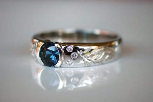 Image of a half bezel ring in recycled platinum featuring a blue Queensland sapphire, 6 white accent diamonds and gum leaf engraving