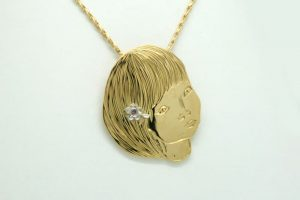 18 Carat recycled yellow gold pendant made in the image of a little girl with a pink diamond and platinum hair clip