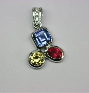 Pendant image. Three bright gemstones bezel set and soldered together with a bale featuring Argyle diamonds. The pendant features an Asscher cut tanzanite, and oval fair trade ruby and a round Australian yellow sapphire. The pendant was handmade as a birth present