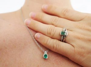 Image of hand and decolletage showing off a Western Australian emerald engagement ring and pendant. The pieces were handmade in recycled palladium and feature Argyle diamonds. By Ethical Jewellery Australia